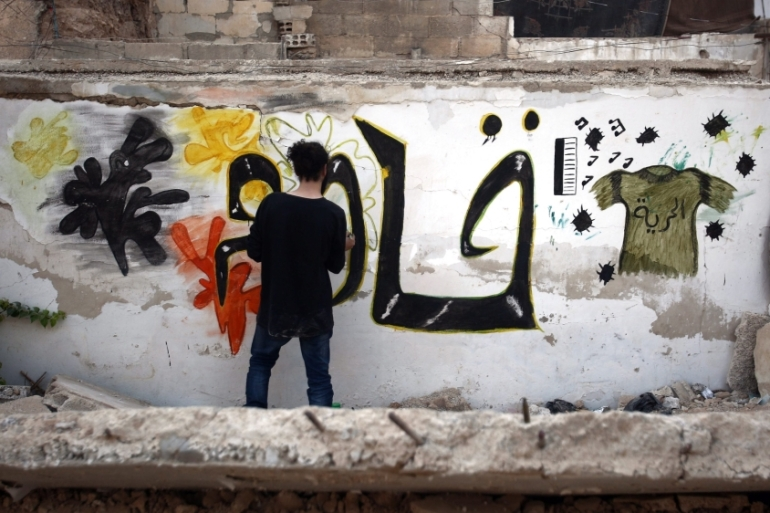 Syrian artist Noor paints graffiti that says 'Resist' on a destroyed wall in rebel-held al-Qaboon neighbourhood, in outskirts of Damascus, [EPA]