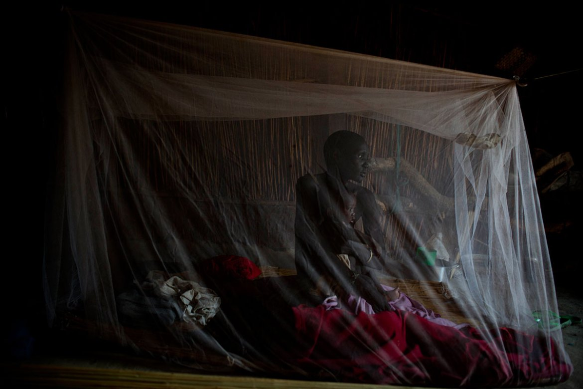 A woman sits with her baby under a mosquito net. This year alone UNICEF and partners have admitted 184,000 children with severe malnutrition for treatment. [Kate Holt/UNICEF]