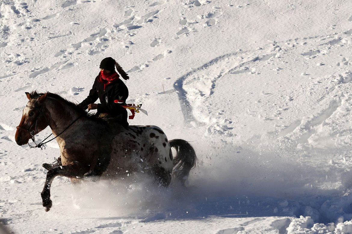 A young Native American man rides his horse through the snow near the Oceti Sakowin camp near Cannon Ball, North Dakota. [Lucas Jackson/Reuters]