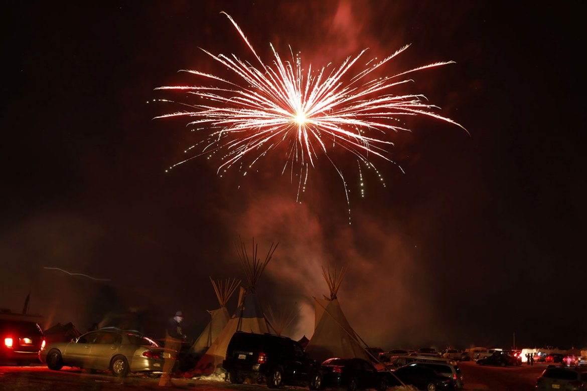 Fireworks explode above tipis inside the Oceti Sakowin camp as celebrations continue after the Army Corps of Engineers denied an easement for the $3.8bn Dakota Access Pipeline to pass adjacent to the Standing Rock Indian Reservation, near Cannon Ball, North Dakota. [Lucas Jackson/Reuters]