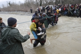 File: Refugees and migrants wade across a river near the Greek-Macedonian border [Stoyan Nenov/Reuters]