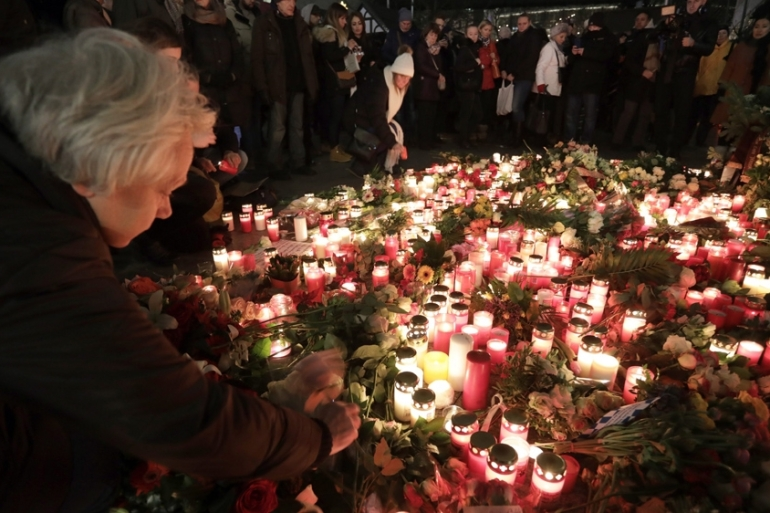 Members of the public light candles at the site of the attack on a Christmas market in Berlin. At least 12 people were killed when a truck drove into a Christmas market [Joerg Carstensen/EPA]