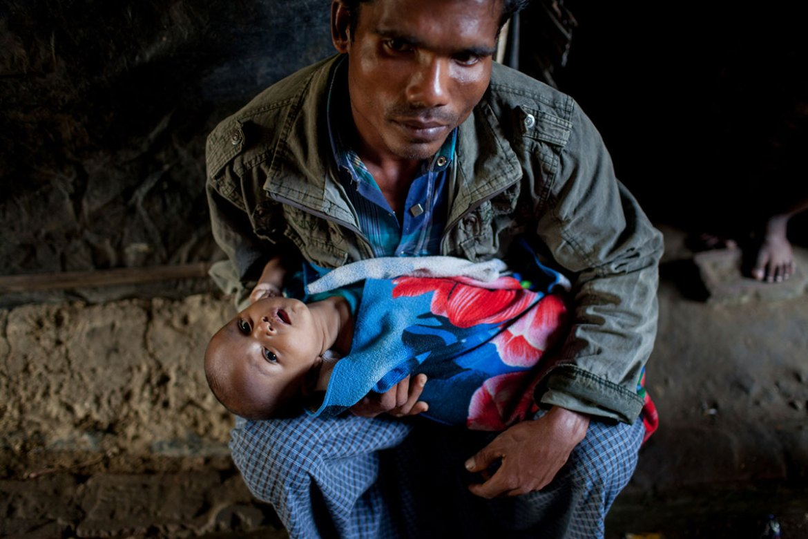 Mohammad Rafiq, 24, holds his eight-month-old baby. His wife was killed in one of the attacks. [Mahmud Hossain Opu/Al Jazeera]