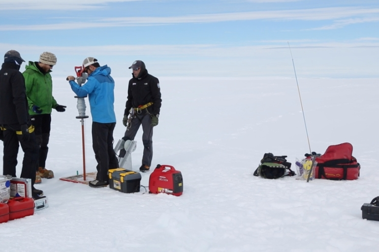 A team uses hand-held drilling gear to sample a solid ice core [Tarek Bazley/Al Jazeera]