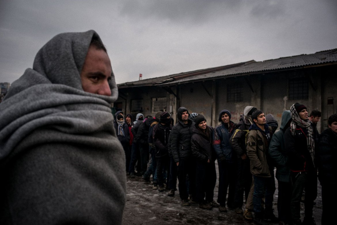 Volunteers works to make sure the refugees receive one warm meal a day. Here the refugees line up to receive the food.  [Federico Scoppa/CAPTA/Al Jazeera]