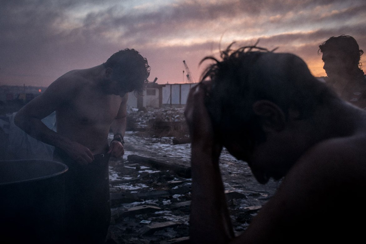 The refugees wash and bathe outside in the cold, warming some water in an old barrel. [Federico Scoppa/CAPTA/Al Jazeera]