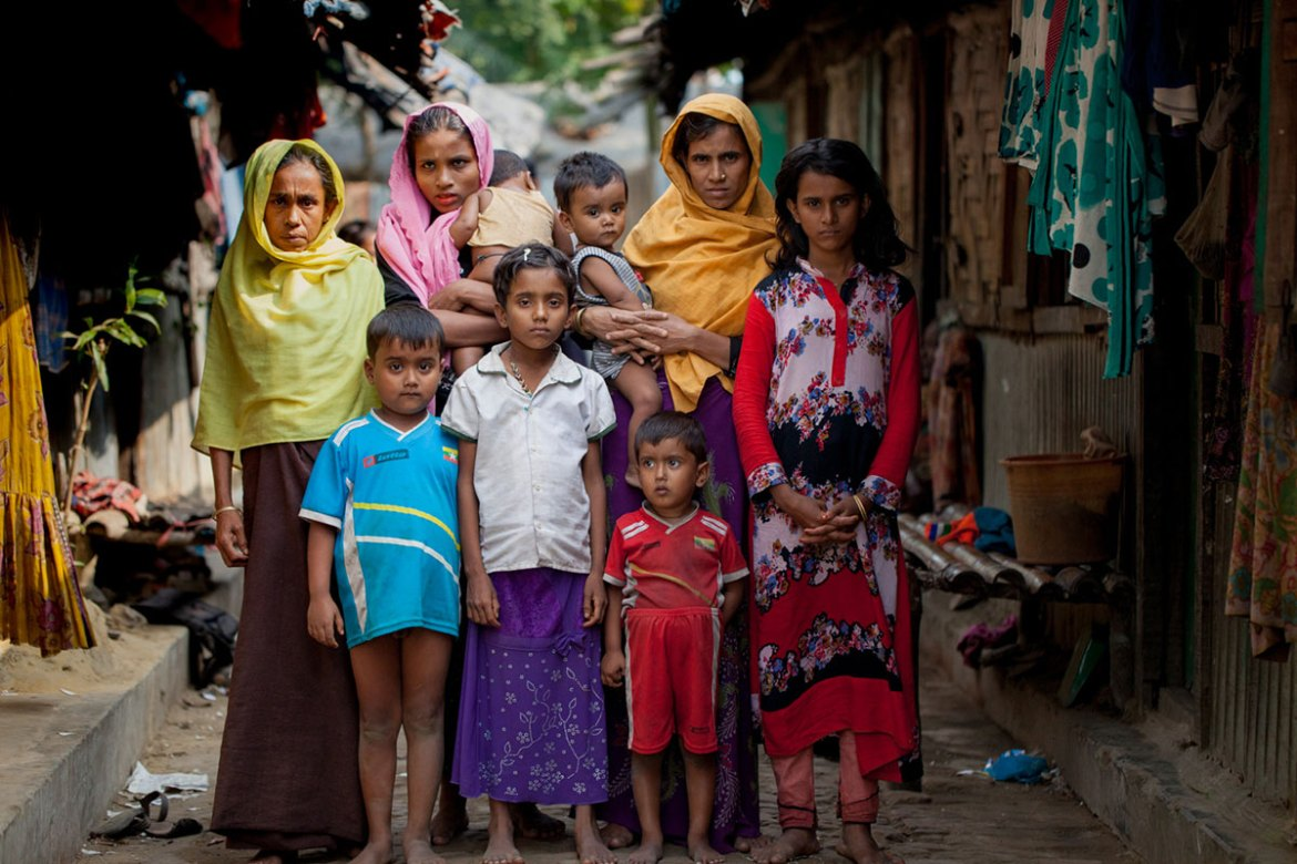 Yesmin, right, 14, poses for a photograph with her family members who were forced to flee Myanmar. Rights group say the military has been running a systematic campaign of violence against Rohingya in western Rakhine state. [Mahmud Hossain Opu/Al Jazeera]