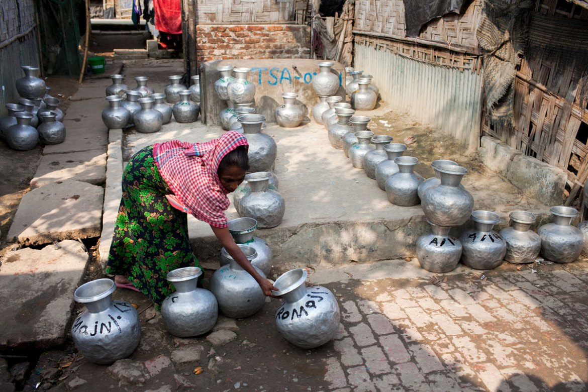 A Rohingya woman places her jar in a queue to collect water at the Leda Rohingya refugee camp in Bangladesh. [Mahmud Hossain Opu/Al Jazeera]