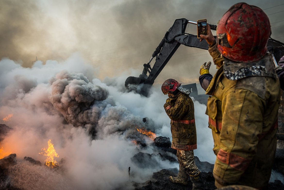 Firefighters stand on the edge of a blazing oil pit as they work to extinguish the flames, while one holds up his phone to take a photo. [Claire Thomas/Al Jazeera]