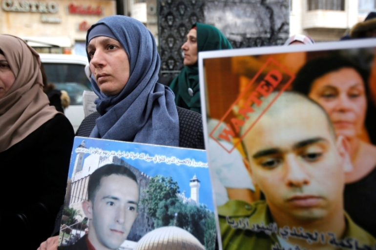 The mother of slain Palestinian Abed al-Fattah al-Sharif holds his poster as another woman holds a poster of Azaria during a protest in Hebron this week [Mussa Qawasma/Reuters]