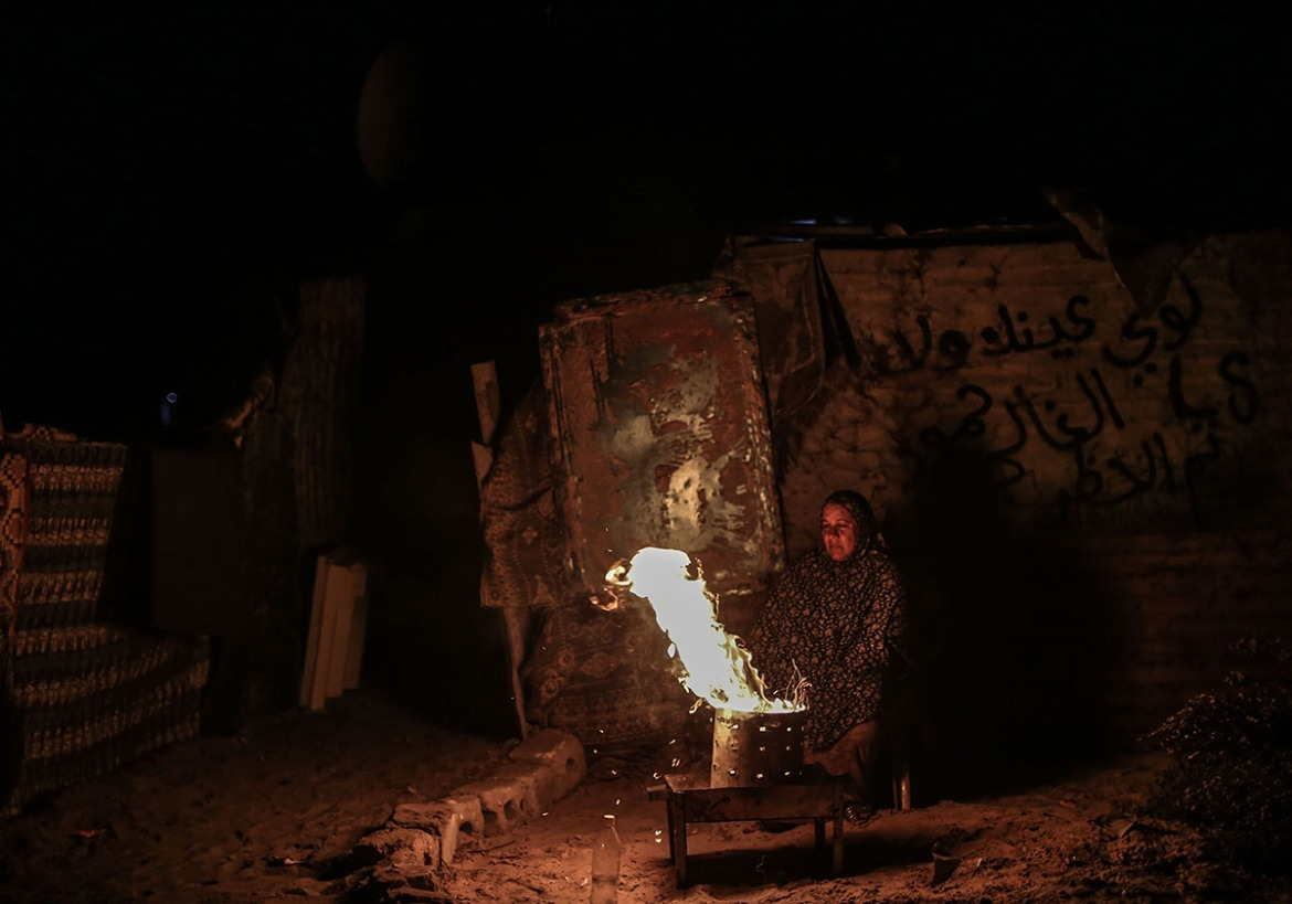 Umm Hamed Zoarob uses the fire for both cooking and lighting their home. 'There's no electricity, there's no gas, there's nothing to do,' she says, explaining that her children are all unemployed, and they cannot afford a generator or fuel. [Ezz Zanoun/Al Jazeera]