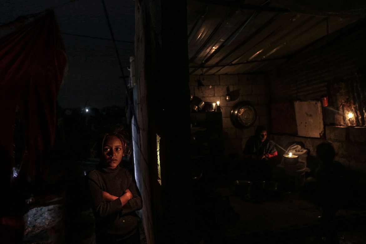 Raghad Abu Nimr lives with her family in an impoverished neighbourhood of Khan Younis. The family of seven rely on candles and battery-operated lights when they can afford to. [Ezz Zanoun/Al Jazeera]
