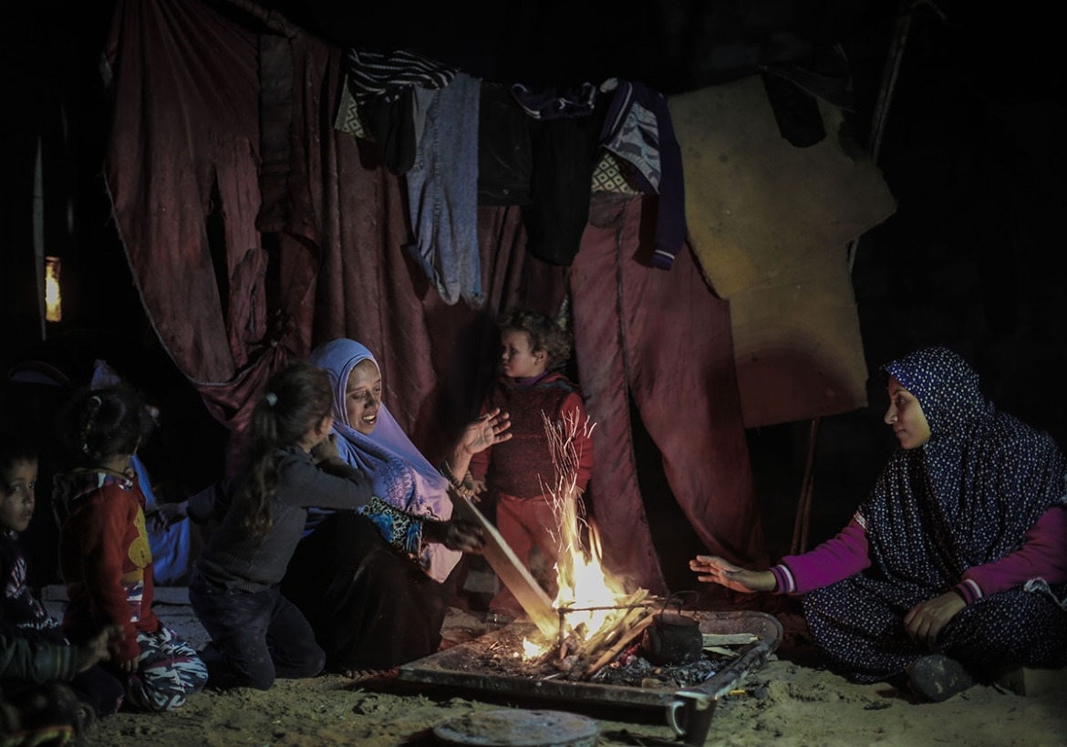 Umm Abdullah, Raghad's mother, sits with her neighbour and Raghad's siblings around a fire. They have no electricity most of the time. [Ezz Zanoun/Al Jazeera]