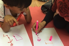 A parent mirrors her child's drawing in a group session designed to help parents to be more attuned to their children's needs [Dania Fawaz/Al Jazeera]