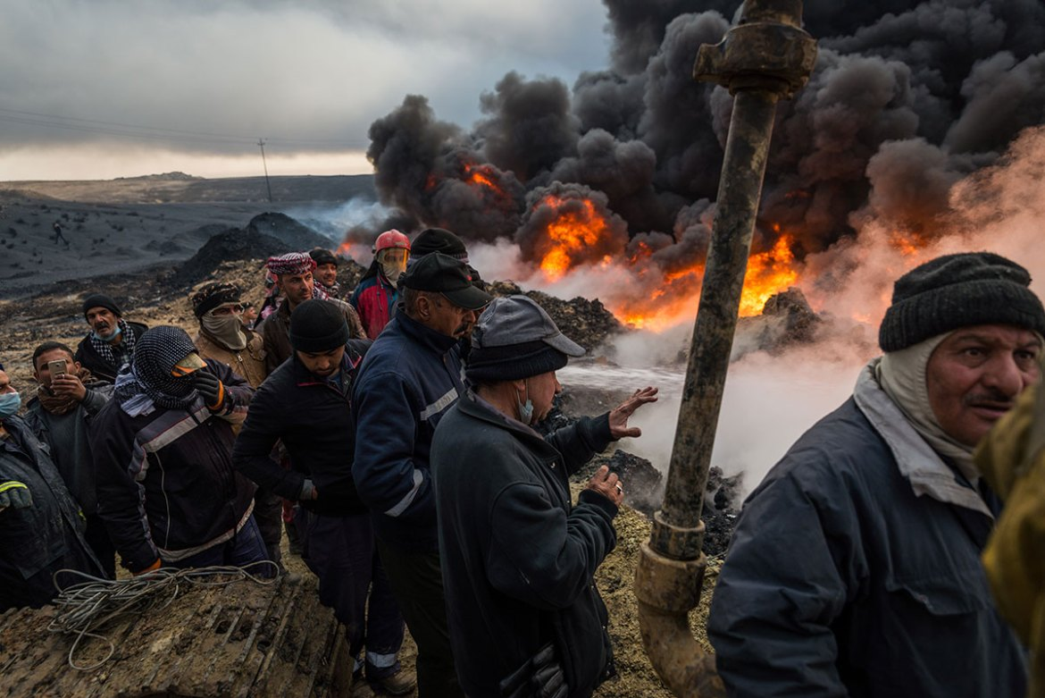 Men gather at the fire's edge as water is pumped into a flaming oil well. [Claire Thomas/Al Jazeera]