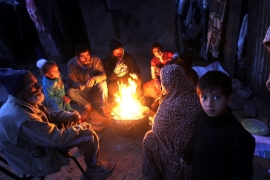 A Palestinian family warms up in front of a fire in the Khan Younis refugee camp, southern Gaza Strip, last month [EPA]