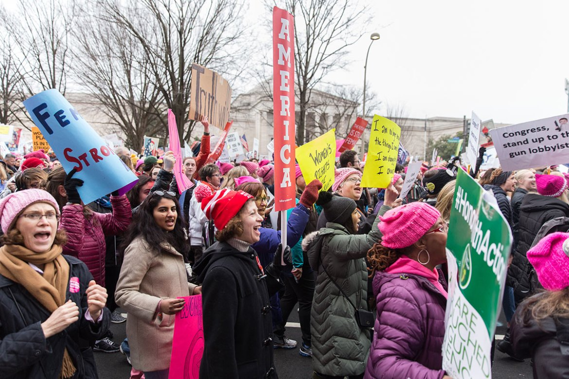 Women chant shortly before reaching the White House, many wearing pink which became the unofficial colour of the march. [Kelly Lynn Lunde/Al Jazeera]