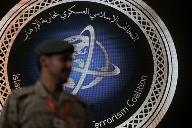 A security officer stands guard in front of the logo of the Saudi-led Islamic Military Counter Terrorism Coalition [Faisal Al Nasser/Reuters]