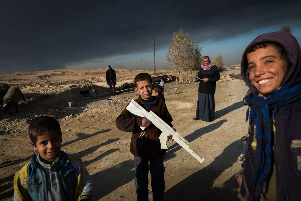Children play near the burning oil wells in Qayyarah. [Claire Thomas/Al Jazeera]