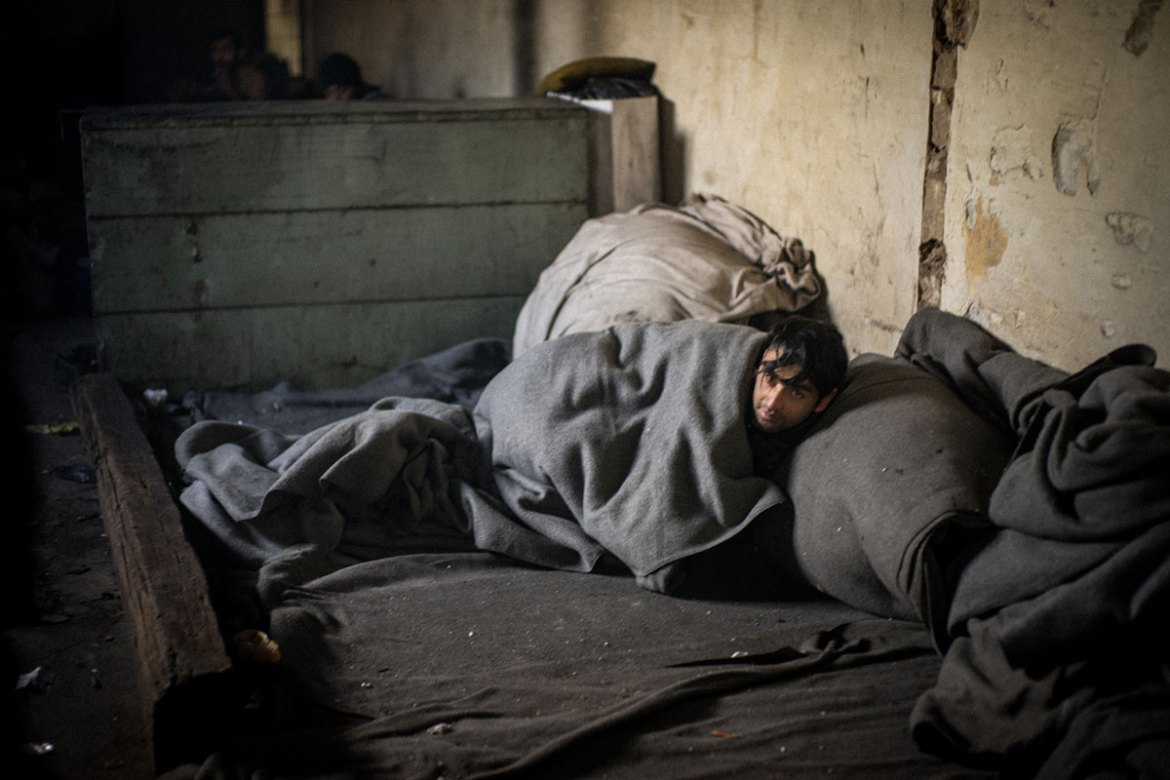 People sleep on the ground, wrapped in blankets distributed by volunteers, while surrounded by garbage and other waste. The sound of coughing echoes through the space. [Federico Scoppa/CAPTA/Al Jazeera]