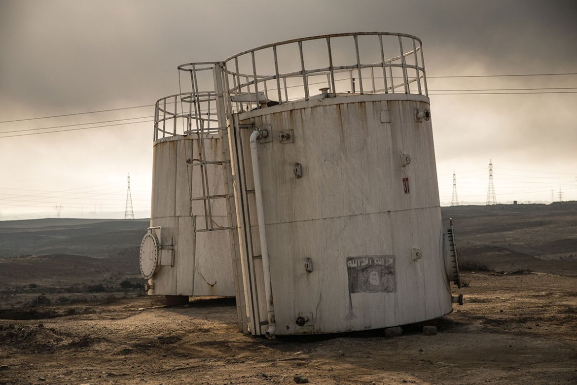 Signs of ISIL are common in Qayyarah, which was under the group's control for more than two years. The ISIL flag is seen painted on an old oil tank by the road leading to the oil wells, a road that was littered with explosives planted by ISIL. [Claire Thomas/Al Jazeera]