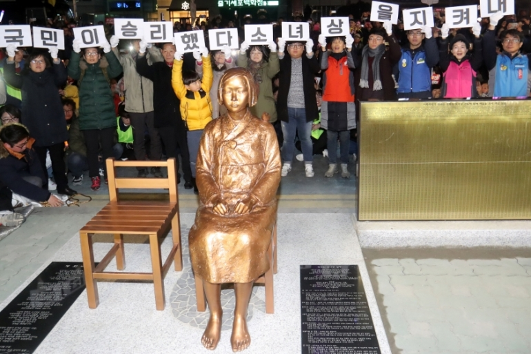 A bronze statue of a seated woman with a bird on her shoulder was placed in front of the Japanese consulate [Yonhap/Reuters]