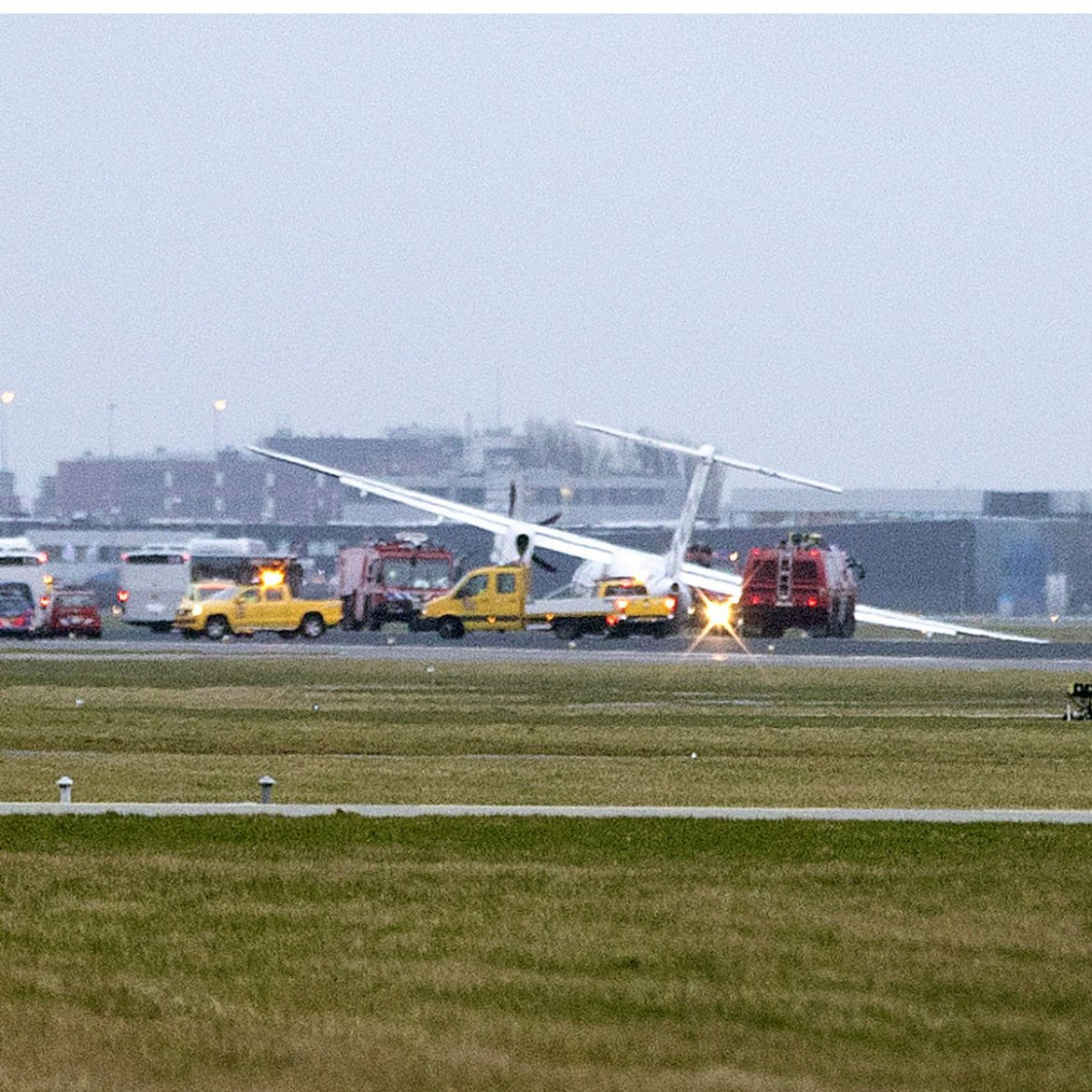 Emergency vehicles arrive after a plane veers off the runway amid a storm at Schiphol Airport. Its landing gear collapsed on approach, but no passengers were injured. [Michel van Bergen/AFP]