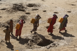 Women carry jerry cans of water from shallow wells dug from the sand along the Shabelle River bed in Somalia's Shabelle region, March 19, 2016 [Feisal Omar/Reuters]