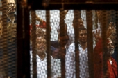Muslim Brotherhood members wave with the Rabaa sign, symbolising support for the organisation, at a court on the outskirts of Cairo [File: Amr Abdallah Dalsh/Reuters]