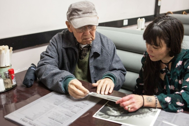 Matsuoka tells Japanese American social justice activist and multimedia artist, Kyoko Nakamaru, about his life in an internment camp for Japanese Americans [Jessica Chou/Al Jazeera]