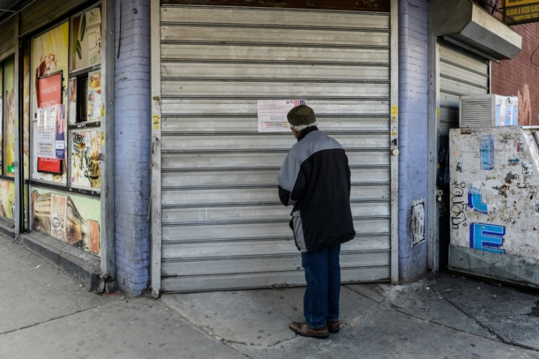 A man reads a sign announcing the closure of a bodega during a Yemeni protest against President Donald Trump's travel ban [Stephanie Keith/Reuters]