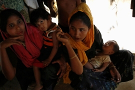 Rohingya refugees sit inside their home at a refugee camp in Bangladesh [M P Hossain/Reuters]