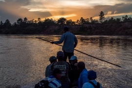 Miskito men cross the Coco River from a refugee community in Honduras back to their native land in Nicaragua [Alex McDougall/Al Jazeera]