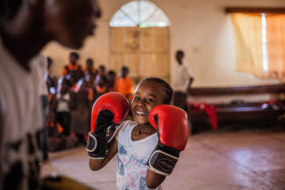 A young participant mentored by Sonko practises the basic boxing stance at Rehema Daycare School and Orphan Centre. [Natalia Jidovanu/Al Jazeera]