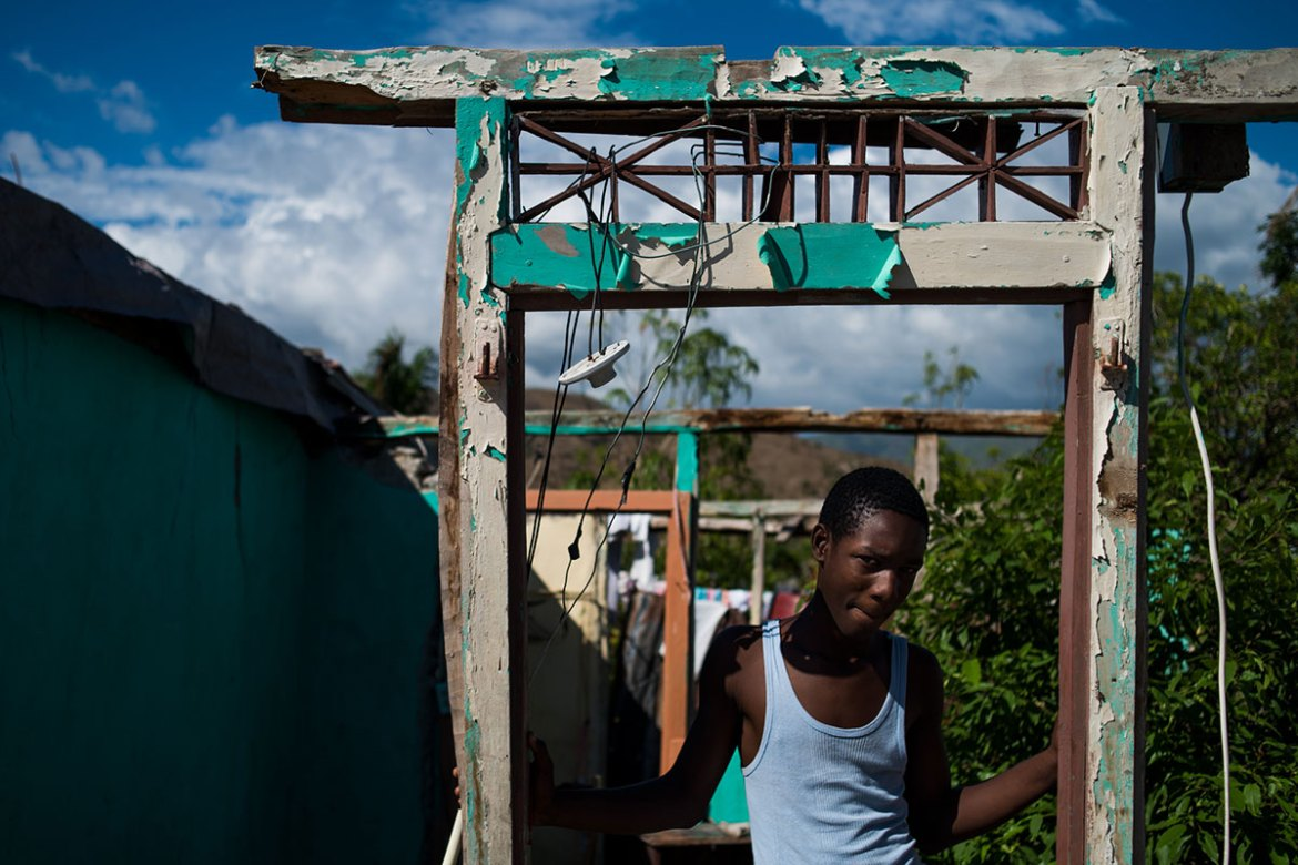 A young boy poses for a portrait in the doorway where his house stood before Hurricane Matthew. [Alex McDougall/Al Jazeera]