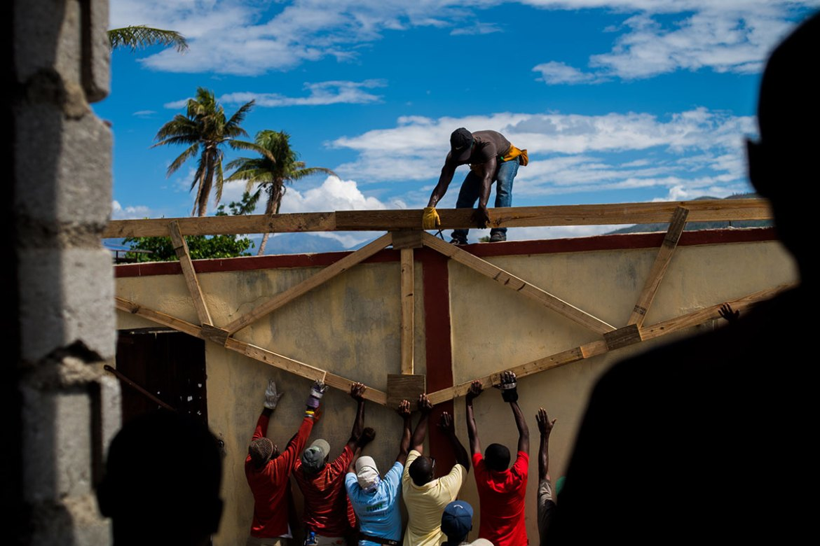 Men work to rebuild the roof of a school that was destroyed by Hurricane Matthew in Les Anglais. [Alex McDougall/Al Jazeera]