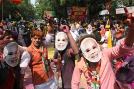 BJP supporters wearing Indian Prime Minister Narendra Modi's mask celebrate as BJP wins in Uttar Pradesh state in the assembly elections on March 11 [EPA]