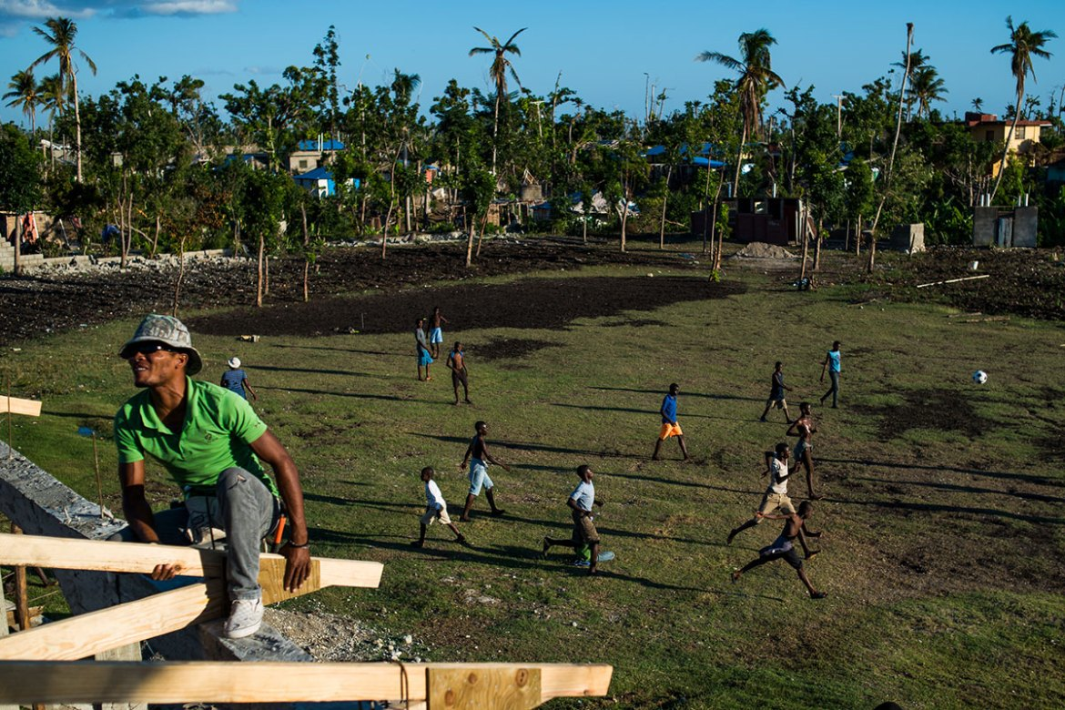 Young boys play football while construction on a schoolhouse continues in Les Anglais. [Alex McDougall/Al Jazeera]