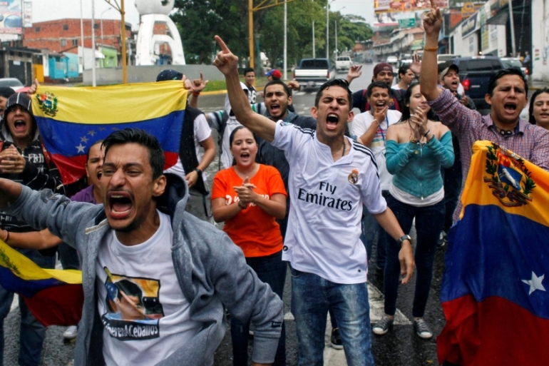 Pockets of protesters blocked roads, unfurled banners and chanted slogans against Maduro [Reuters]
