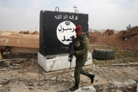 An Iraqi soldier walks next to a wall painted with the black flag commonly used by ISIL, near Arabi neighbourhood, north of Mosul, Iraq, January 21 [Khalid al Mousily/Reuters]