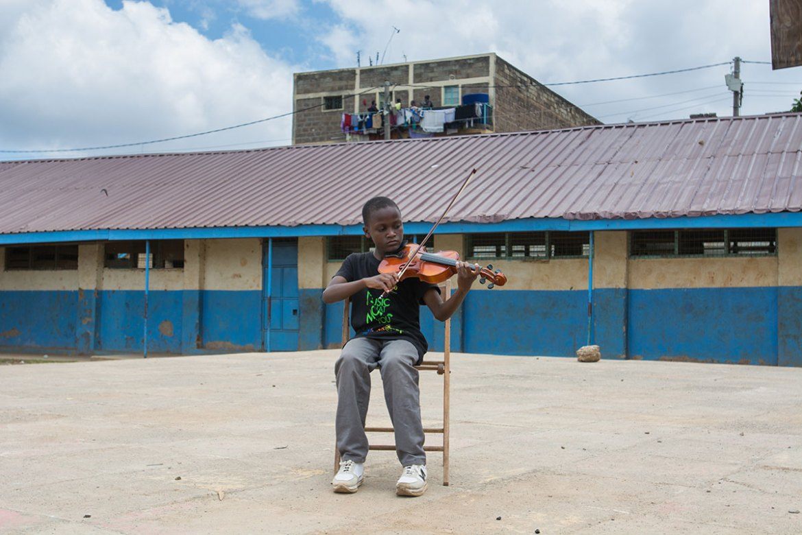Kennedy, 13, is making music in the playground of a primary school. 'I hope the violin will take me to places I've never been before. I want to become a great musician.' [Eva de Vries/Al Jazeera]