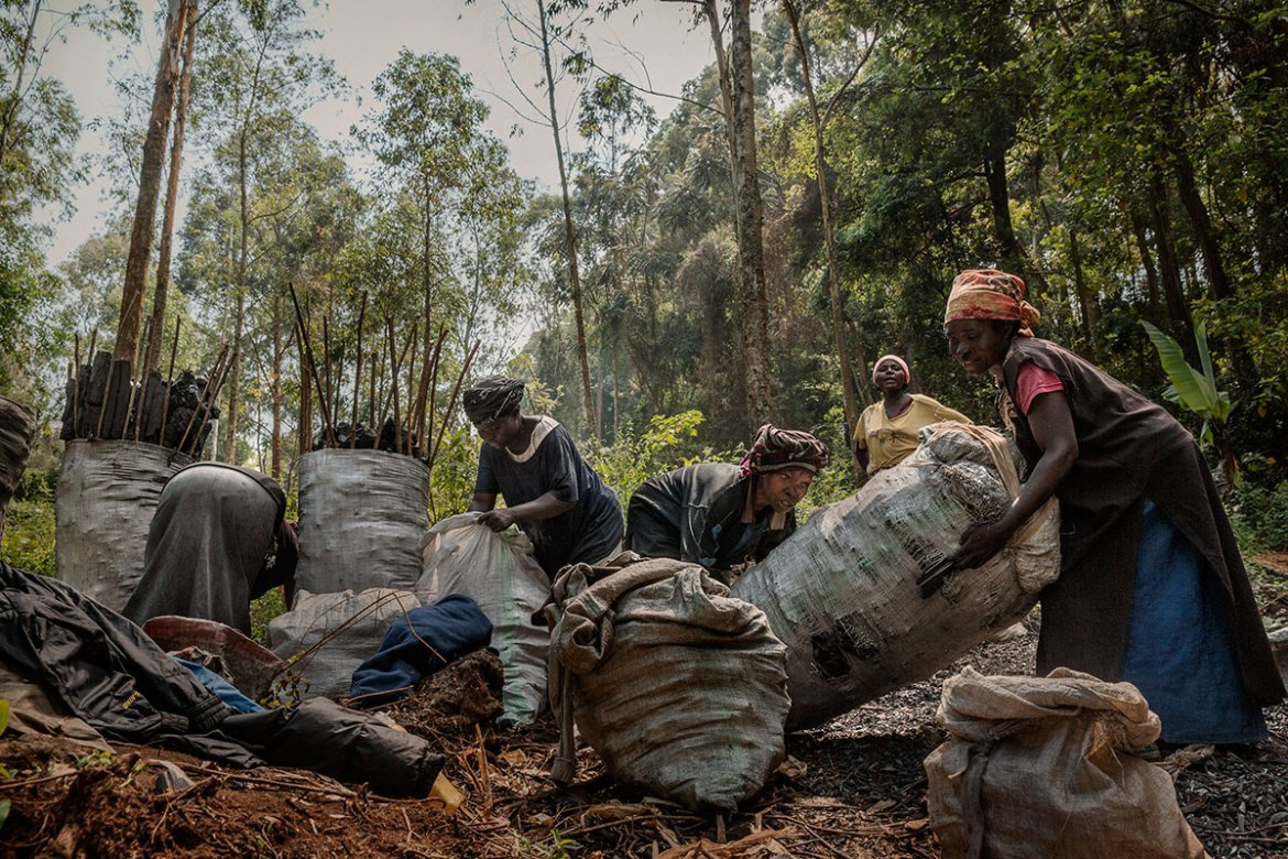 This group of women will carry coal - that can weigh as much as 60kg - on their backs for kilometres up steep roads, from the forests to the nearest villages, earning about $2 a day. [Marco Gualazzini/Al Jazeera]