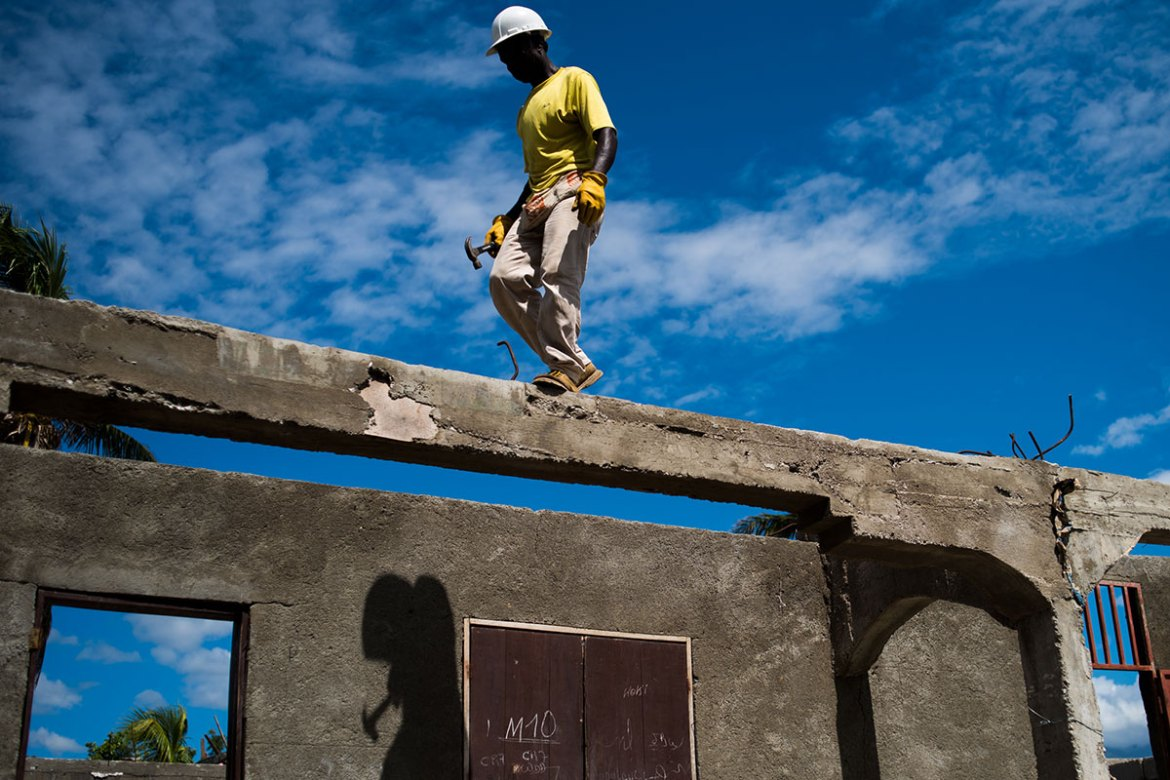 A man works to rebuild the roof of a schoolhouse that was destroyed by Hurricane Matthew. [Alex McDougall/Al Jazeera]
