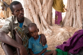 Ahmed Osman and his son Mohamed, seek medical care for Mohamed in Duho, where a small clinic is serving pastoralist families affected by malnutrition [Ashley Hamer/Al Jazeera]