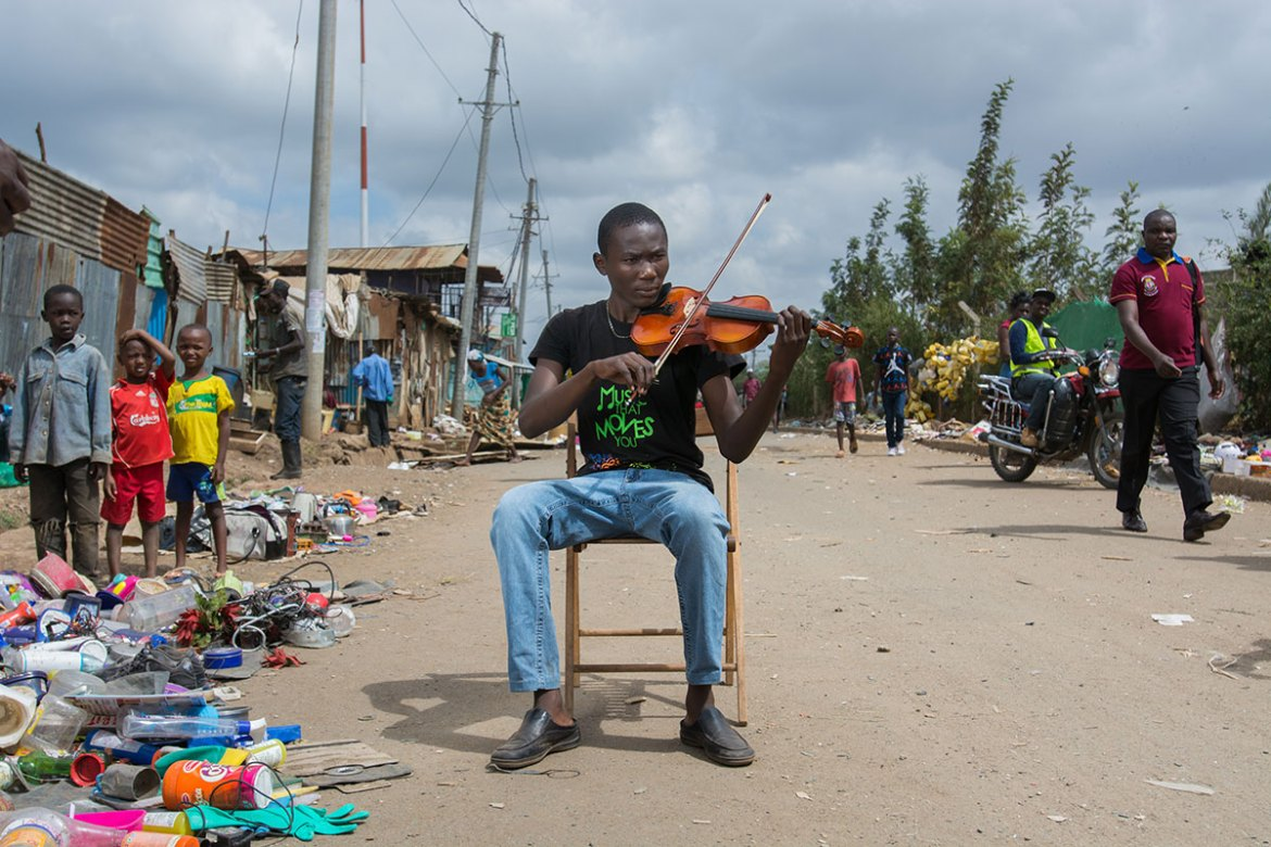 Julius,18, is playing the violin in the streets of Korogocho. 'Making music keeps me busy. If I didn't play, I would probably be hanging out on the streets,' he says. [Eva de Vries/Al Jazeera]
