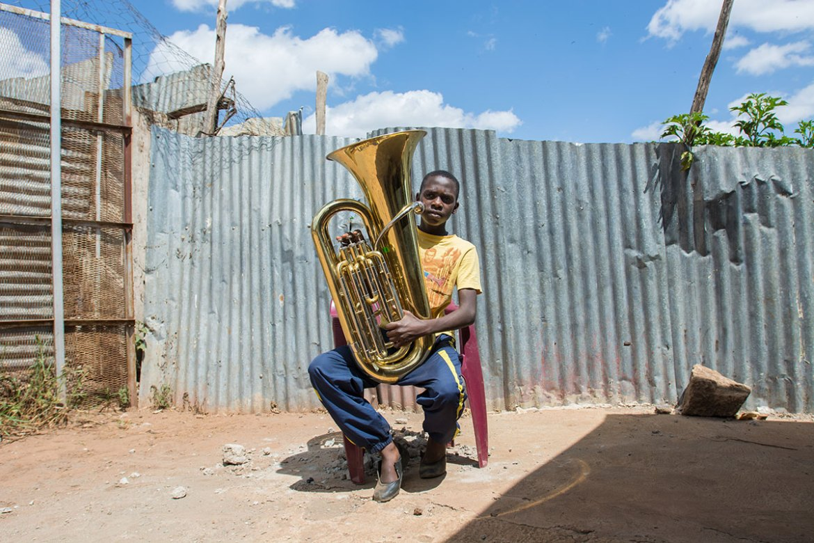 A large rubbish dump lies just on the other side of the wall. Despite the foul smell, Miquel, 14, still loves playing the tuba. 'It's my dream to have my own 10 years from now.' [Eva de Vries/Al Jazeera]