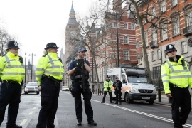 Police officers stand guard on a road leading to the Houses of Parliament in London on Thursday [Kirsty Wigglesworth/AP]