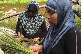Leena collecting reeds from the nearby marshland [Aishath Niyaz/Al Jazeera]