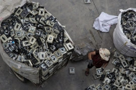 A worker distributes electronic waste at a government managed recycling centre at the township of Guiyu in China's southern Guangdong province June 10, 2015 [Reuters]