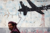 A man walks past a graffiti, denouncing strikes by US drones in Yemen, painted on a wall in Sanaa, February 6 [Khaled Abdullah/Reuters]